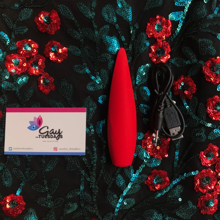 Red hot Ember unpackaged beside charger and business card all set upon sequin floral backdrop.