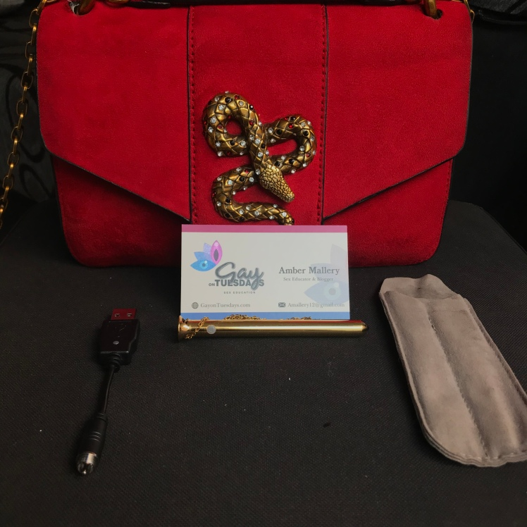 Vesper Crave front and center of a ruby red purse while various tools surround Vesper Crave