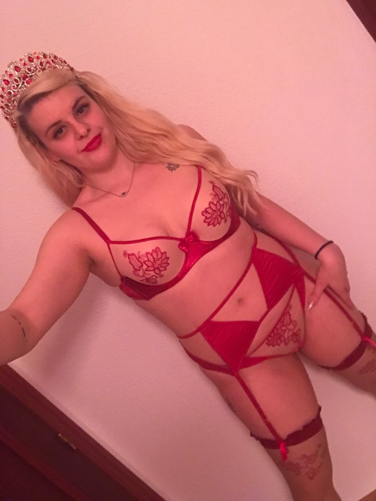 Me in peach and red accented lingerie, standing with hand on my hip and a smirk