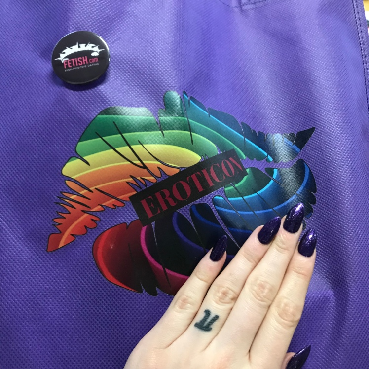 Purple Eroticon bag with rainbow kiss print, Fetish dont com on off to the side with my matching purple nails