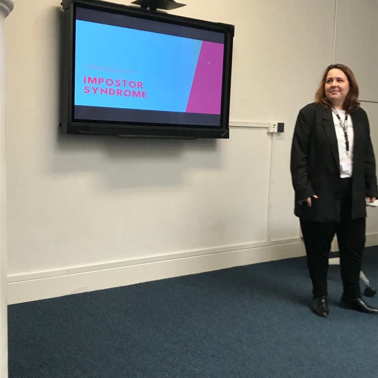 Photo of sex educator Natalia standing next to a presentation slide on impostor syndrome