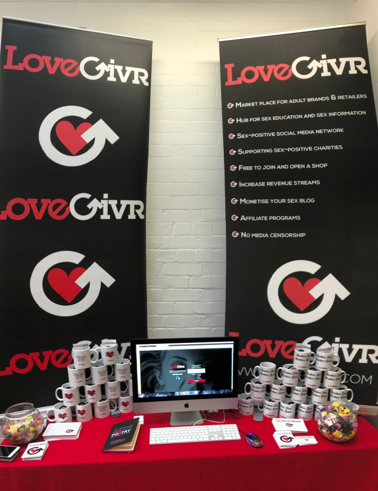LoveGivrs booth, covered in candy, mugs, and a computer for sign up