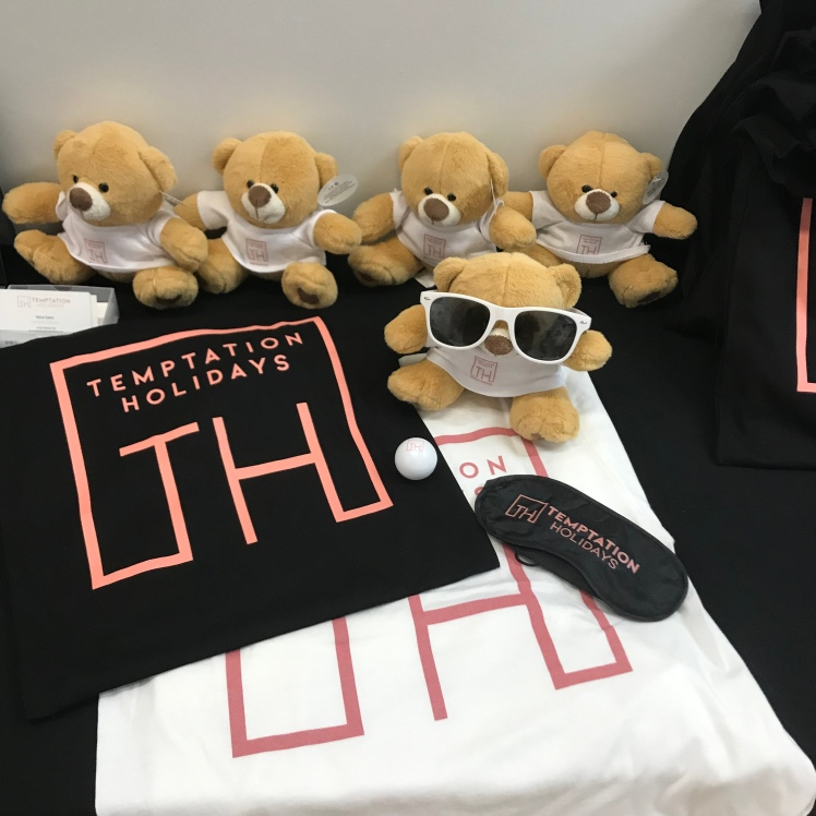 "A table of Temptation Holidays March, including white tee shirts with ""Temptation Holidays"" printed in pink across the back. A cute teddy bear and some sunnies"