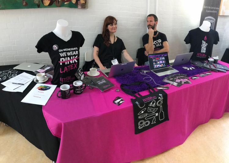 Fetish dot coms booth covered in pink and black bags, shirts, and assorted merch
