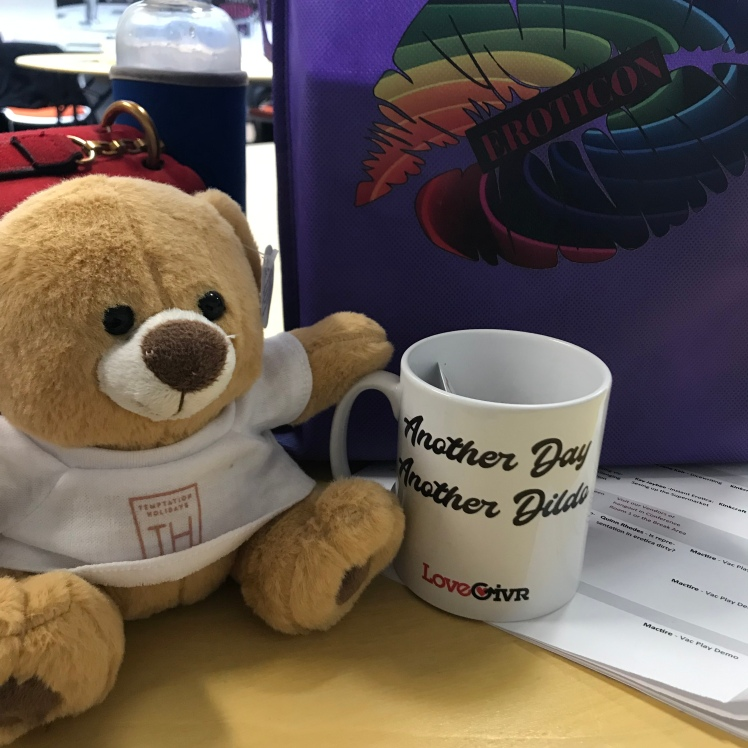 Temptations Holiday bear, Teddy Holiday next to a purple Eroticon swag bag and Lovegivr mug
