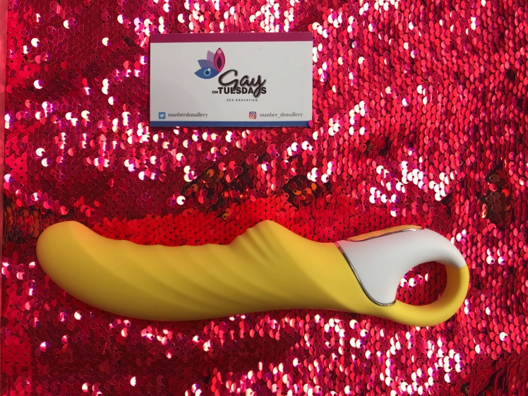 Satisfyer Yummy Sunshine, placed horizontally on a sunset colored sequin backdrop.